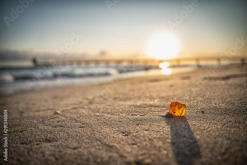 Bernstein im Sonnenaufgang am Strand Fototapet