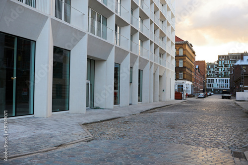 Carta da parati Deserted city street with modern white residential building along paved cobblestone sidewalk early in the morning with sun rising on cloudy sky in background
