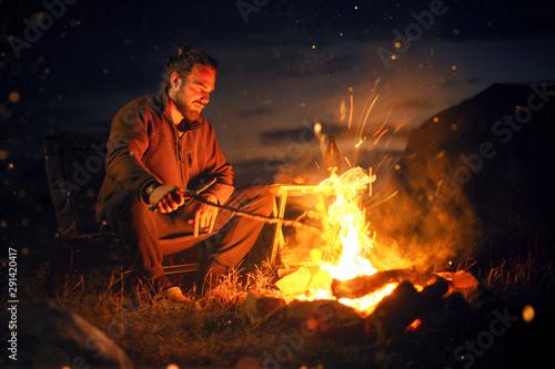 Man sitting next to a bonfire in the dark Fototapete