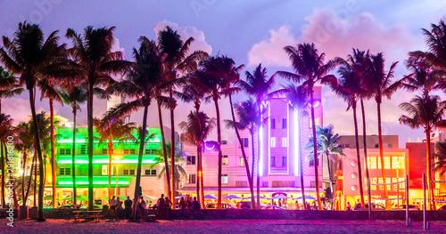 Fototapeta premium Hotele i restauracje w Miami Beach Ocean Drive o zachodzie słońca. Panoramę miasta z palmami w nocy. Życie nocne w stylu art deco na południowej plaży