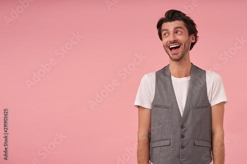 Happy young dark haired man wearing grey waistcoat and white t-shirt, standing o Fototapeta