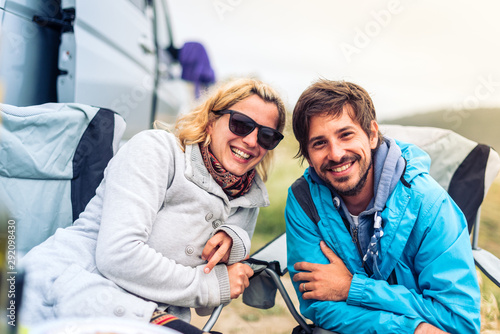 Canvas Print Young couple smiling with motorhome, RV or campervan on beach.