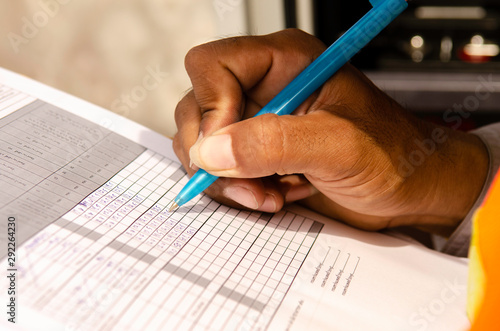 Photo close-up of technician fill the maintenance form,Engineer write data in maintenance check list