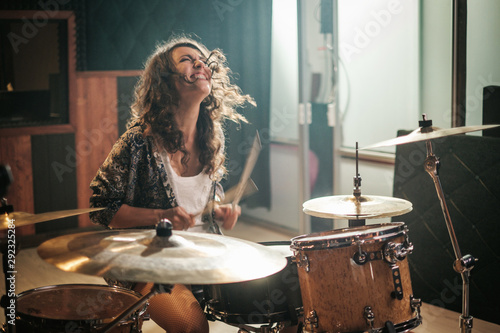 Fotografiet Woman playing drums during music band rehearsal