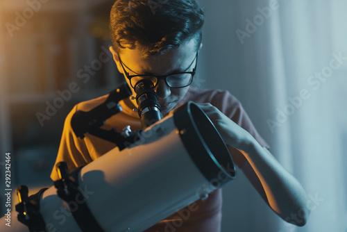 Foto Smart boy using a telescope and watching stars