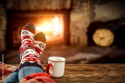 Photo Woman legs with christmas wool socks and fireplace