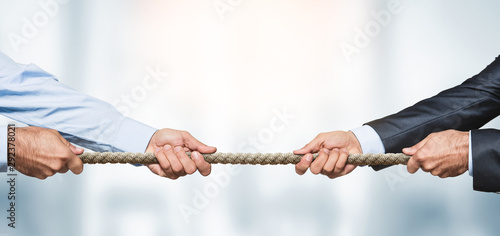 Tableau sur Toile Tug of war, two businessman pulling a rope in opposite directions over defocused