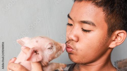 Photo Young male teren kissing a piglet.  Vegan concept.