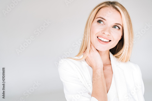 Fotografia smiling beautiful young blonde woman in total white outfit looking away isolated