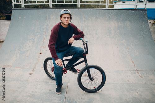 Fotografia Professional young sportsman cyclist with bmx bike at skatepark