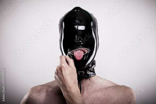 Canvas Print submissive man open the zipper of his black shiny rubber mask
