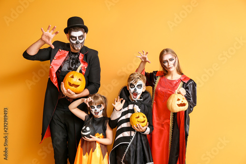 Obraz na płótnie Family in Halloween costumes and with pumpkins on color background