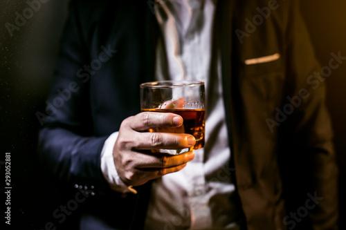 фотография Closeup businessmen holding a glass of whiskey