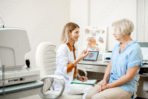 Obraz na plátně Senior woman patient talking with female ophthalmologist during a medical consultation at the ophthalmologic office