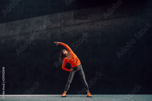 Full length of fit attractive caucasian woman in sportswear standing wide-legged, holding one hand on hip and doing side stretch in front black wall Fototapeta
