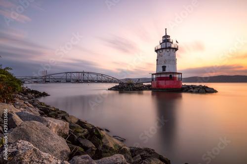 Obraz na plátně Caisson (sparkplug) style lighthouse under soft golden light with a bridge in the background