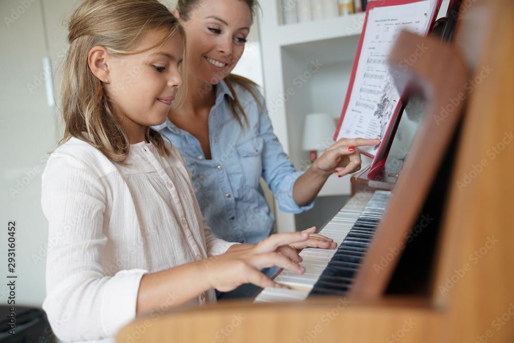 Mała dziewczynka bierze lekcję gry na pianinie, nauczyciel ją obserwuje <span>plik: #293160452   autor: goodluz</span>