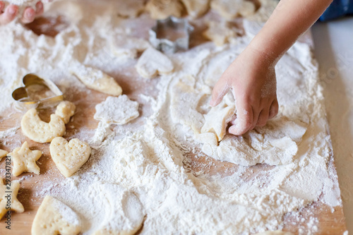 Child hands are cooking Christmas gingerbread cookies in home kitchen Fototapeta