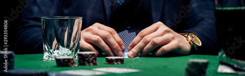 Photo panoramic shot of man holding playing cards near glass and poker cards