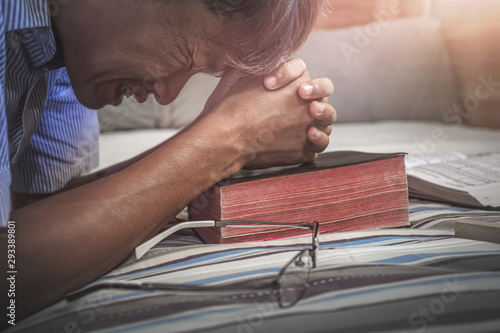 Photo Close up young christian praying on old Bible, Want to help from God