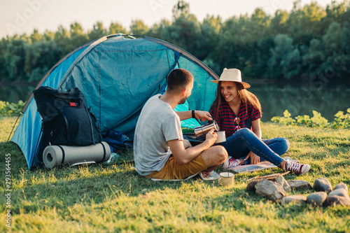 Leinwand Poster friends on camping outdoor by the lake or river
