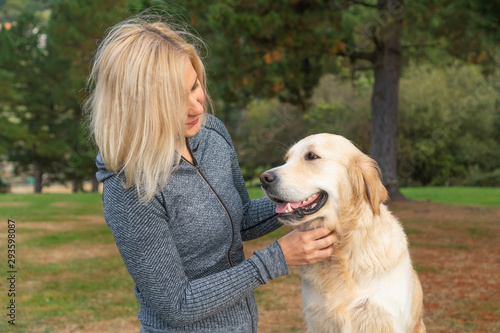 A girl in sportswear caresses a golden retriever dog and looks with care Fototapet