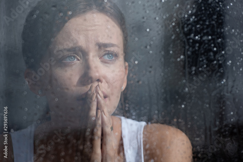 Foto selective focus of upset young woman crying and showing please gesture at home