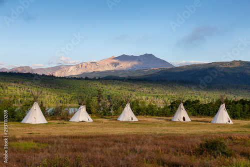 Canvas Print Beautiful View of the Tipi in a field with American Rocky Mountain Landscape in the background during a sunny summer morning