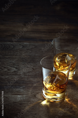 Photographie close up view of  two glasses with ice and whiskey on wooden background
