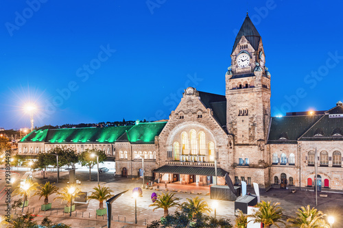 31 July 2019, Metz, France: Night view of the illuminated old railway station building with clock tower in Metz city