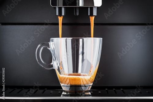 freshly brewed coffee is poured from the coffee machine into glass cup