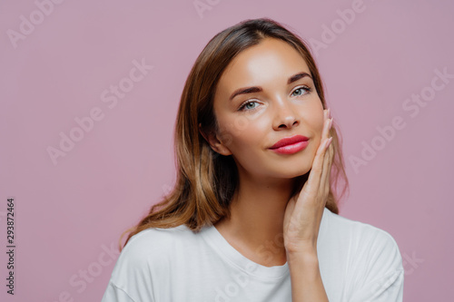 Headshot of lovely female model touches gently cheek, enjoys delicate face skin, wears makeup, has manicure, cares about her beauty, looks straightly at camera, dressed in white jumper, models indoor