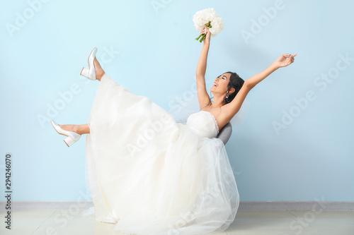 Tela Happy young Asian bride near color wall