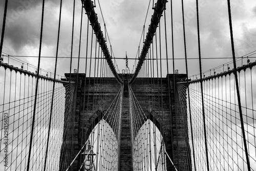 Fototapeta premium Brookyln Bridge Nowy Jork Manhattan czarno-biała grafika w skali szarości niebo chmury inżynier budowlany East River widok punkt orientacyjny kable podwieszane statyka łuki filary pilon murowane symetria