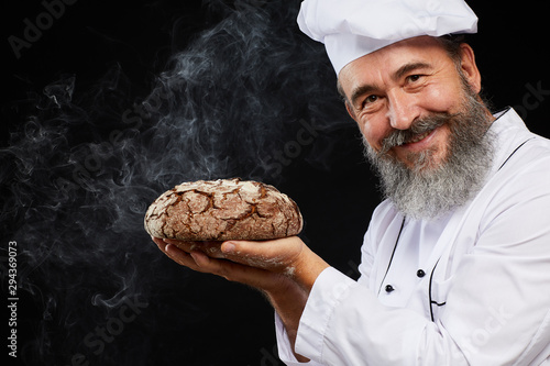 Portrait of charismatic bearded baker holding fresh bread loaf while standing ag Fototapete