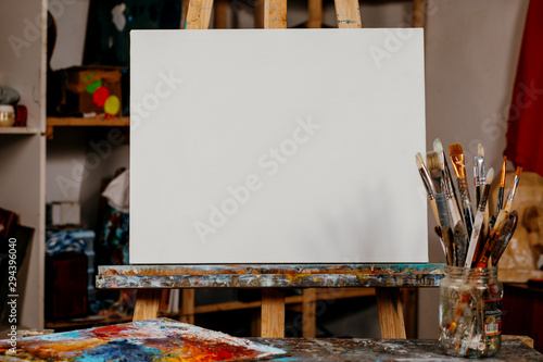 Canvas Print Art equipment: easel, brushes, tubes with paint, palette and paintings