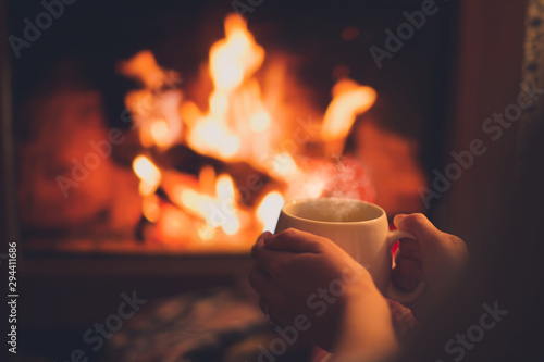 Photo Cup of tea in woman's hands sitting near fireplace