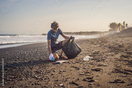 Young man cleaning up the beach. Natural education of children Fototapeta