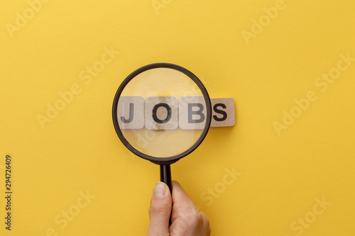 Photo cropped view of woman holding magnifying glass under cardboard squares with jobs