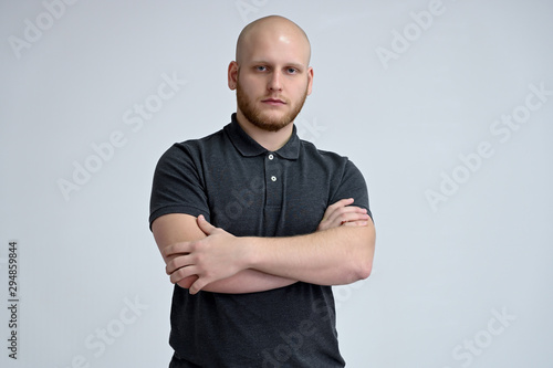 Fototapeta Portrait of a handsome bald man in a gray t-shirt on a white background in the studio