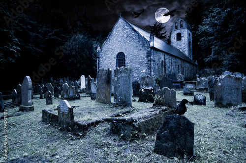 Fotografija old graveyard with ancient tombstones grave stone and old church front of full m