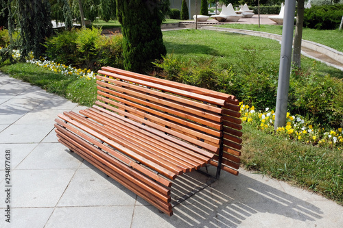 Obraz na płótnie Beautiful comfortable wooden bench of brown slats with a smooth transition