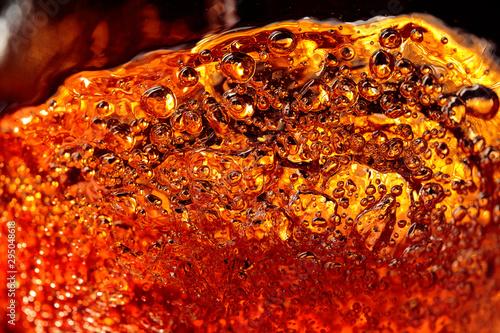 Fotografia Alcoholic drink on a dark background, abstract splashing.