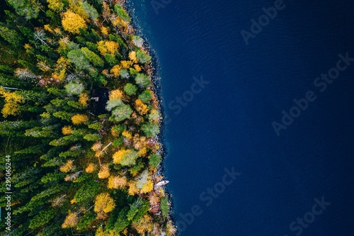 Aerial view of cottage in autumn colors forest by blue lake in rural Finland Fototapeta