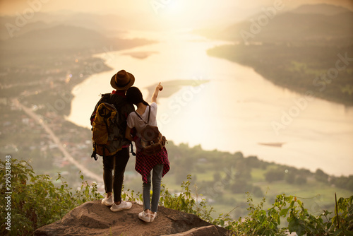 фотография couple backpacker standing on cliff with sunset background