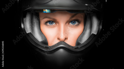 Fotografia Close up view of a woman face in biker helmet.
