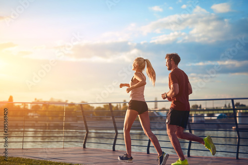 Canvas Print Modern woman and man jogging / exercising in urban surroundings near the river