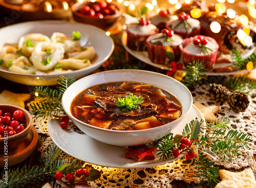 Christmas mushroom soup, a traditional vegetarian  mushroom soup made with dried forest mushrooms in a ceramik plate on a festive table Fototapeta