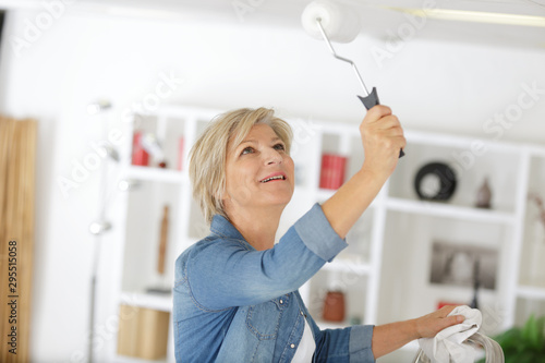 mature woman using roller to paint the ceiling Fototapeta