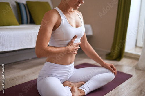 Fotografia Close-up of woman sitting on exercise purple mat in lotus position while eyes closed and breathtaking